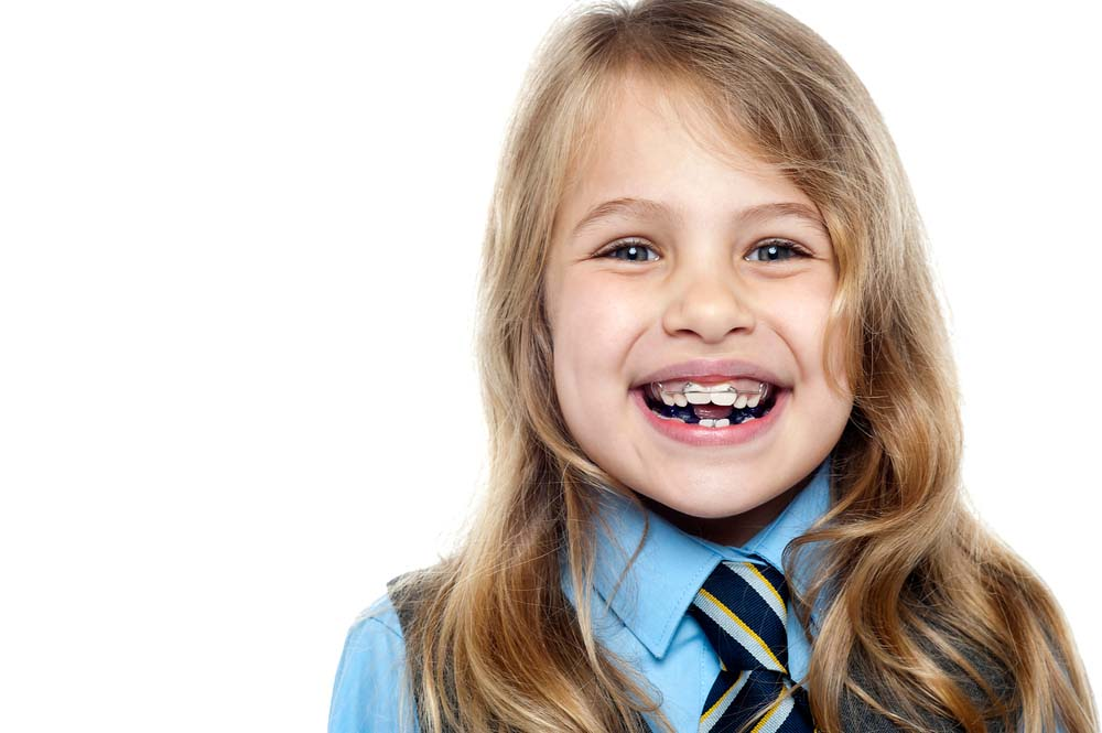 little girl in school uniform wearing her wire retainer braces