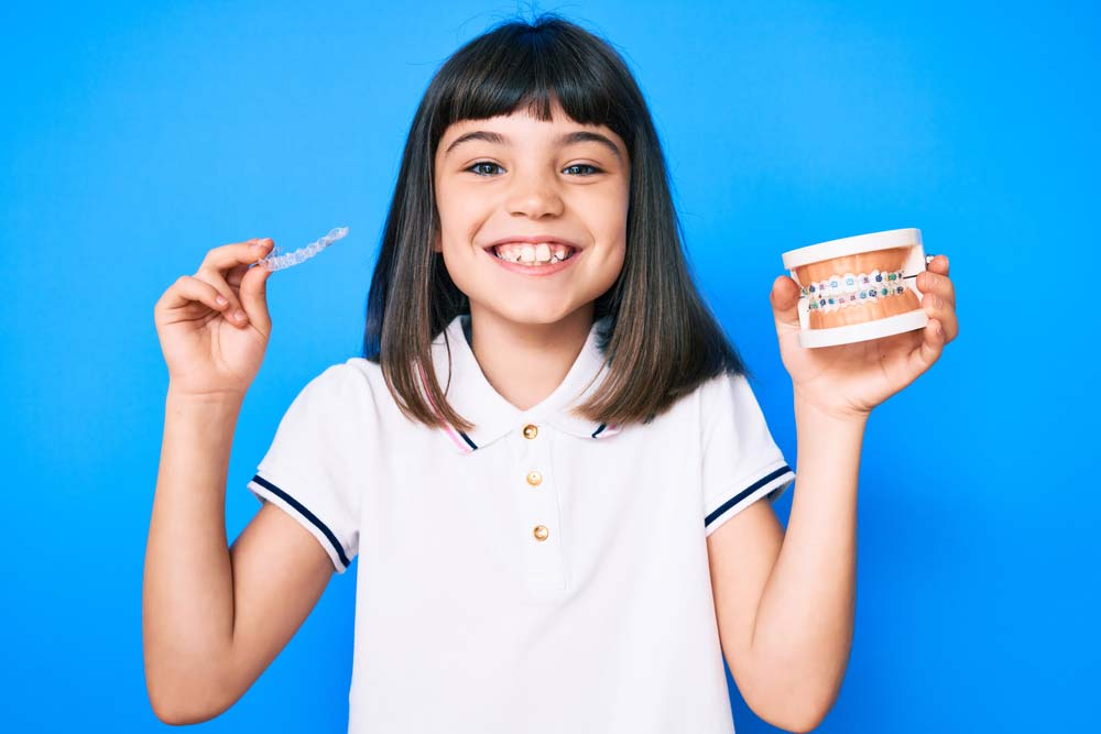 girl smiling with her HSE grant free clear retainer and braces mould