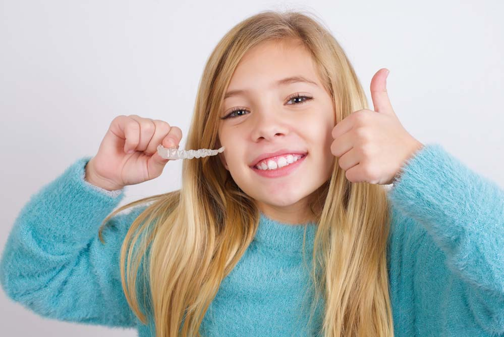 girl smiling with her clear Invisalign retainer