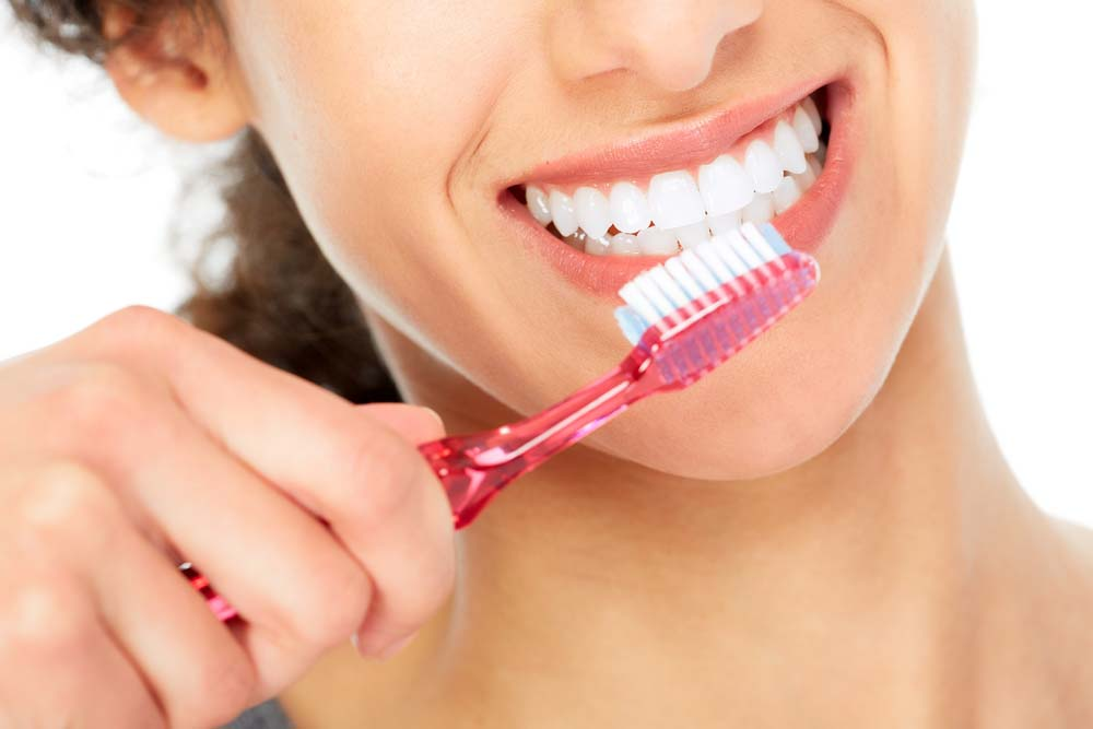woman demonstrating how to brush teeth