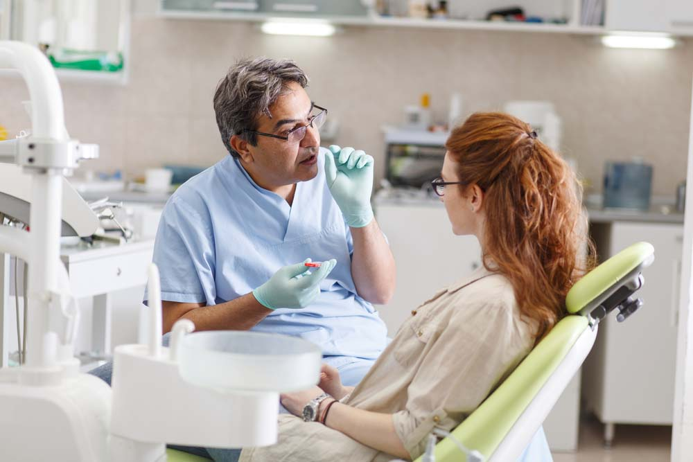 male orthodontist examine female patient